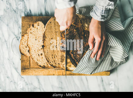 Female hands cutting freshly baked sourdough bread into pieces - Stock Photo