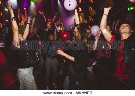 Milennials dancing and partying in nightclub - Stock Photo