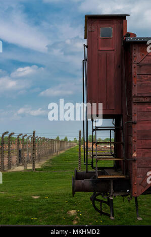 Details of lonely train wagon in Auschwitz II Birkenau, nazi concentration camp in Poland. Barbed wire and buildings in the background. - Stock Photo