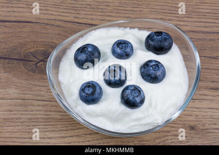 Sweet bilberries in plain yoghurt. White yogurt in the glass bowl with delicious blueberries on a vintage wooden background. - Stock Photo