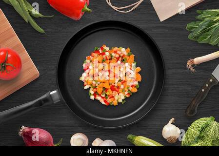 Frying pieces of vegetables in a pan. Preparing ingredients for head dish. Vegetarian cuisine. Top view. - Stock Photo