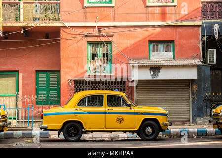 KOLKATA - INDIA - 22 Jan 2018: An Ambassador yellow cab taxi is parked in the street under a red-colored house in Kolcata, India - Stock Photo