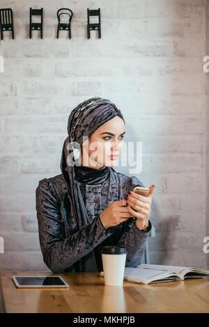 muslim hijab women holding smartphonephone. thinking of good memories. - Stock Photo