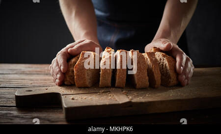chef holding a bread in front of a wooden cutting board - Stock Photo