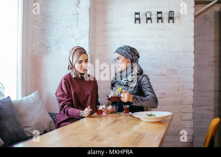 two Pretty caucasian muslim woman drinking tea in cafe - Stock Photo