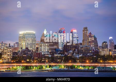 View of Manhattan skyline illuminated at dusk. New York City, USA. - Stock Photo