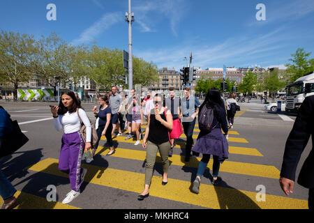People crossing a busy street on a crosswalk in Zurich, Switzerland, Europe - Stock Photo