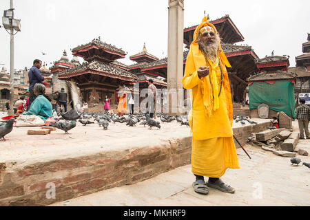 KATHMANDU - NEPAL 08 APRIL 2018. Sadhu in colourful clothes and painted face standing on Durbar Square asking for alms in Kathmandu, Nepal. - Stock Photo
