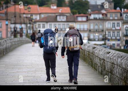 Rear view of two pilgrims heading to Santiago de Compostela using the portuguese way, Ponte de Lima, Portugal - Stock Photo