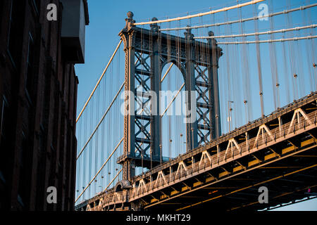 Close-up view of the Brooklyn bridge seen from a narrow alley during the sunset. New York City, USA. - Stock Photo