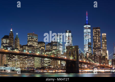 Brooklyn Bridge and the illuminated Skyline of Manhattan in the evening with blue sky and smooth water surface shot from Brooklyn side, New York, Usa. - Stock Photo