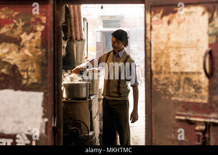 NEW DELHI - INDIA - 11 JANUARY 2018. An Indian man is preparing the famous Masala chai. Is a flavoured tea beverage made by brewing black tea with a m - Stock Photo