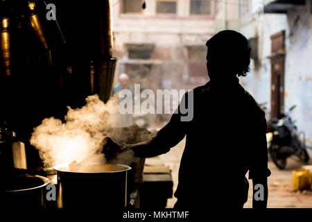 NEW DELHI - INDIA - 11 JANUARY 2018. Silhouette of an Indian man preparing the famous Masala chai. Is a flavoured tea beverage made by brewing black t - Stock Photo