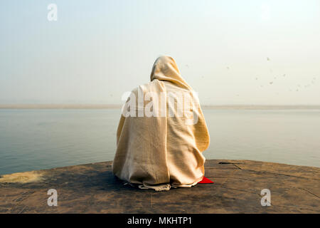 A holy man dressed in white is praying and meditating on one of the many Ghats of Varanasi in front of the sacred river Ganges, India. - Stock Photo