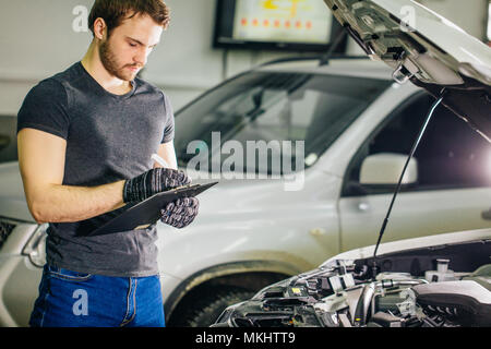 Mechanic standing in front of an open car hood with clipboard and pen - Stock Photo