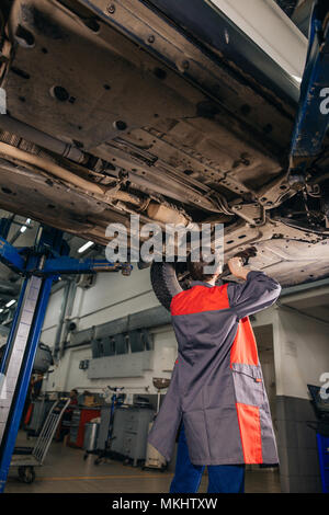 Auto mechanic working at auto repair shop under car with tool - Stock Photo