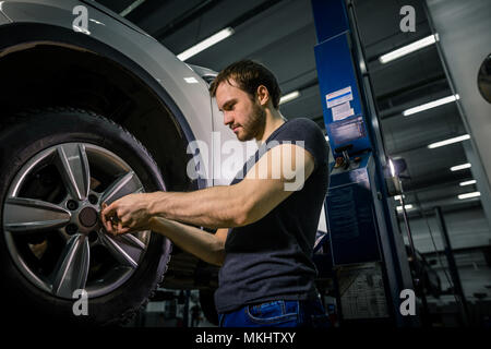 close up Auto mechanic hands in gloves working under hood in garage - Stock Photo