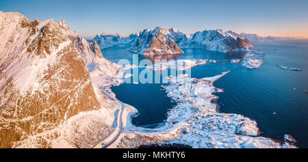 Aerial panoramic view of amazing Lofoten Islands winter scenery with famous Reine fishing village in beautiful golden morning light at sunrise, Norway - Stock Photo