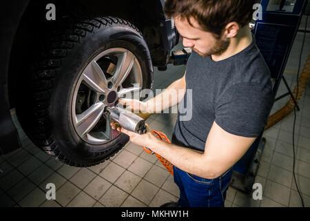 car mechanic changing car wheel in auto repair garage - Stock Photo