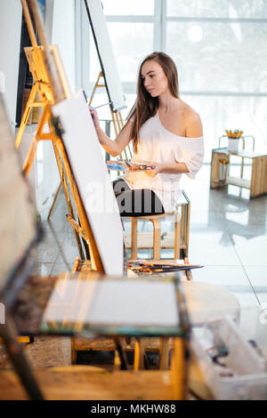 Artist, a European girl painting on easel at art school. Concept teaching painting. - Stock Photo
