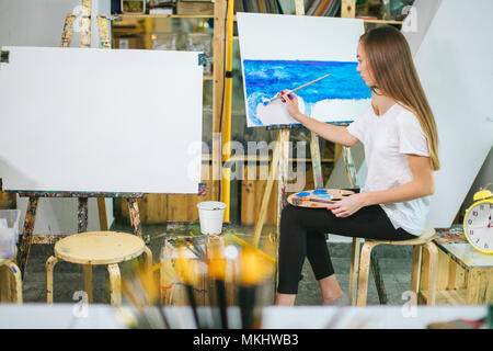 female artist paints picture on canvas with oil paints in her workshop - Stock Photo
