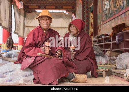 Tibetan monks spinning prayer wheels, Yarchen Gar, Sichuan, China - Stock Photo