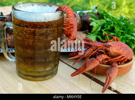 Foamy beer in a glass and boiled crawfish closeup, grilled meat on skewers in the background. For the holidays, enjoying the outdoors. - Stock Photo
