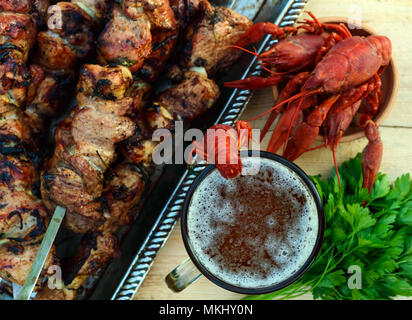 Foamy beer in a glass and boiled crawfish closeup, grilled meat on skewers in the background. The top view. For the holidays, enjoying the outdoors. - Stock Photo