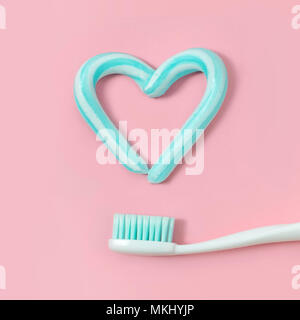 Toothbrushes and turquoise color toothpaste in shape of heart on pink background. Dental and healthcare concept. - Stock Photo
