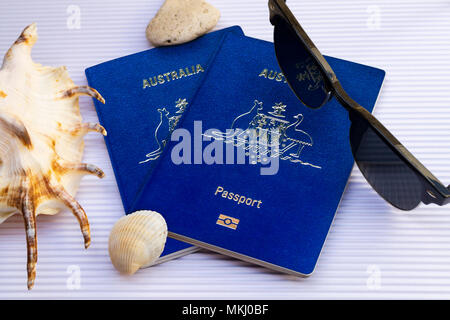 Flat lay two Australian passports with sunglasses and seashells on white cardboard background. Top view. Travel creative concept - Stock Photo