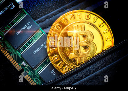 Coin with bitcoin characters and computer circuit board in a wallet, Münze mit Bitcoin-Zeichen und Computerplatine in einem Portemonnaie - Stock Photo