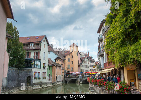 Tourists walk along the Thiou river, Annecy old town. Often called Venice of the Alps due to the beautiful medieval architecture, and canals. - Stock Photo