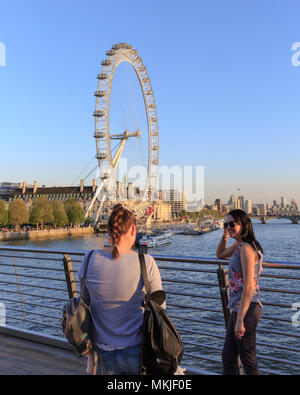 South Bank, London, 7th May 2018. The London Eye proves a popular photo subject in the soft afternoon sunlight. Tourists and Londoners enjoy the sunny weather on the South Bank of London by the river Thames, with record breaking temperatures of up to 28 degrees. Credit: Imageplotter News and Sports/Alamy Live News - Stock Photo