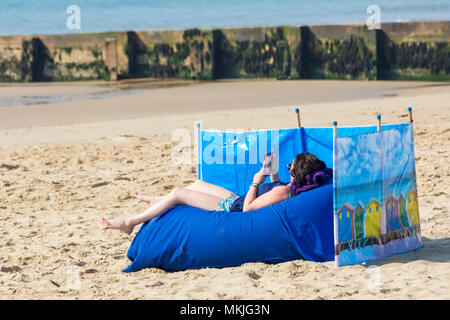 Bournemouth, Dorset, UK. 8th May 2018. UK weather: warm sunny start to the day, as a young woman relaxes on the beach at Alum Chine beach reading her kindle. Credit: Carolyn Jenkins/Alamy Live News - Stock Photo