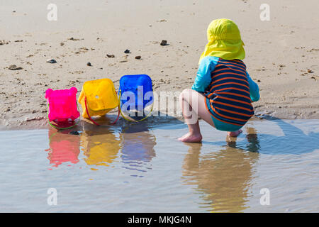Bournemouth, Dorset, UK. 8th May 2018. UK weather: warm sunny start to the day, as a young lad (aged 4) enjoys playing at the seaside with a game of throw the stones and shells into the buckets on the seashore at Alum Chine beach. Credit: Carolyn Jenkins/Alamy Live News - Stock Photo