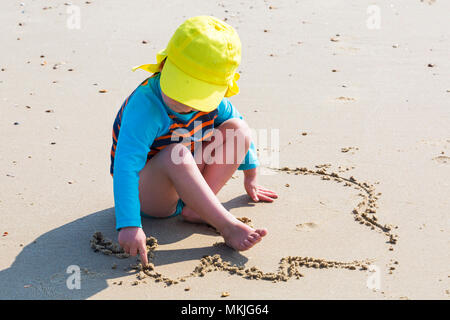 Bournemouth, Dorset, UK. 8th May 2018. UK weather: warm sunny start to the day, as the a young lad (aged 4) draws in the sand with his finger at Alum Chine beach. Credit: Carolyn Jenkins/Alamy Live News - Stock Photo