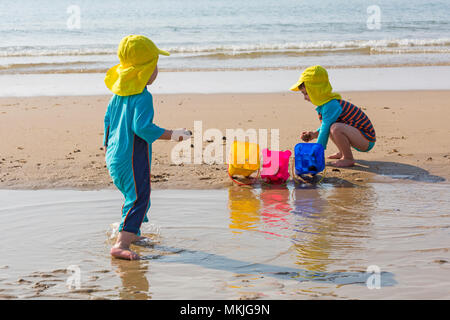Bournemouth, Dorset, UK. 8th May 2018. UK weather: warm sunny start to the day, as two young lads (aged 4 and 2) enjoy playing at the seaside with a game of throw the shells and stones into the buckets on the seashore at Alum Chine beach. Credit: Carolyn Jenkins/Alamy Live News - Stock Photo