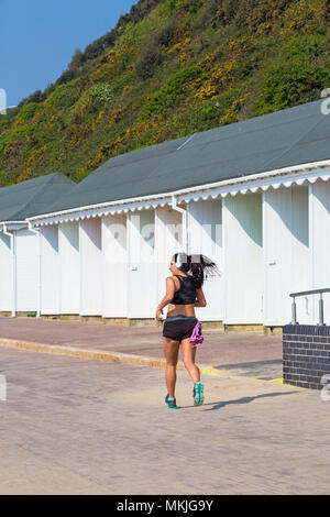 Bournemouth, Dorset, UK. 8th May 2018. UK weather: warm sunny start to the day, as a young woman jogs along promenade past beach huts. Credit: Carolyn Jenkins/Alamy Live News - Stock Photo
