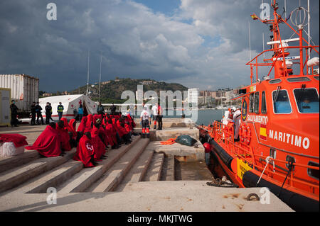 Malaga, Spain. 8th May, 2018. A general view of the Malaga Port as migrants are seen resting after their arrival at Malaga port during the World Red Cross day. Aboard of a boat, members of the Spanish Maritime Safety rescued a total of 57 migrants (of them, 10 womens and two possible minors) near the Malaga coast and brought at Port of Malaga, where they were assisted by the Spanish Red Cross. Credit: Jesus Merida/SOPA Images/ZUMA Wire/Alamy Live News - Stock Photo