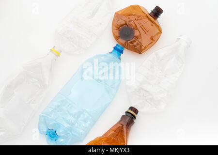 Different types of crushed plastic bottles on white background. Recyclable waste. Recycling, reuse, garbage disposal, resources, environment and ecolo - Stock Photo
