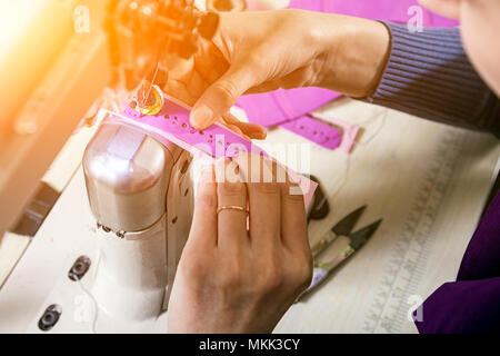 Close-up of a young woman working as a seamstress in a purple unifrome sews genuine leather children's shoes on a sewing machine, top view - Stock Photo