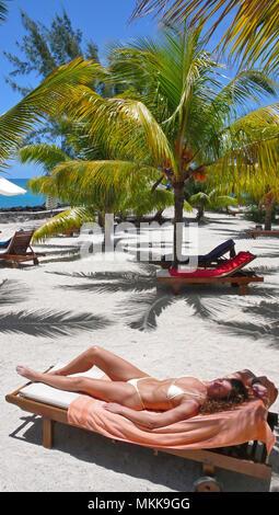 Sonnenbad unter Palmen am Strand im Hotel Hibiscus, Ort Pereybere, Nordwesten von Mauritius - Stock Photo