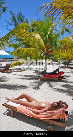 junge Frau sonnt sich unter Palmen am Meer | young woman sunbathing under palmtrees on a lounger at a sandy beach - Stock Photo