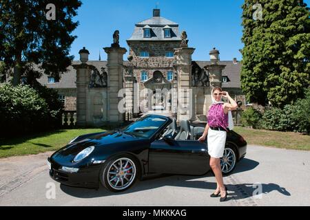 stylish woman and Porsche 911 in front of castle, 911 carrera, 4S, convertible car, sportscar, luxurious | Frau mit Porsche 911 Cabrio vor Schloss, Po - Stock Photo