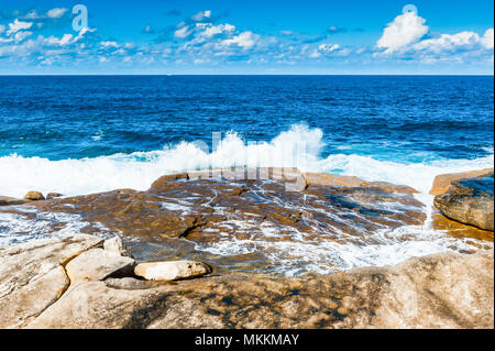 The stunning views along the famous Coogee Beach walk near to Bondi Beach, New South Wales, Australia. Waves crashing on the rocks with a beautiful bl - Stock Photo