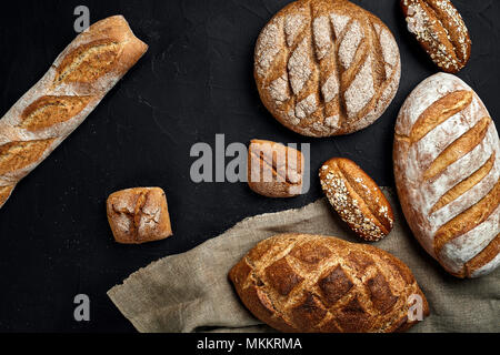 Bakery - gold rustic crusty loaves of bread and buns on black chalkboard background. - Stock Photo