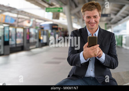 Businessman at the sky train station in Bangkok, Thailand - Stock Photo