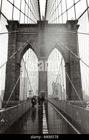 Brooklyn Bridge in the rain photographed in black and white, New York City, NY, United States of America. - Stock Photo