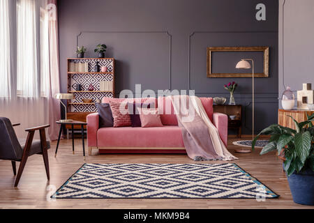 Pink sofa with two blankets and cushions standing in sitting room interior with windows with curtains, patterned carpet and empty frame on the wall - Stock Photo