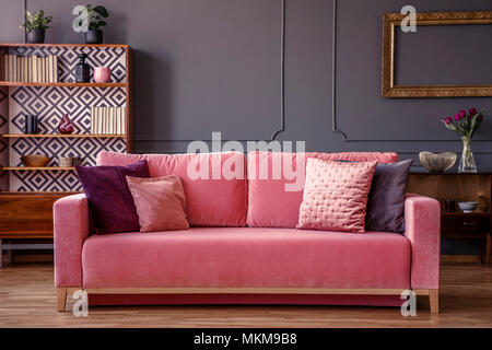 Decorative pillows on pink couch standing in dark living room ...